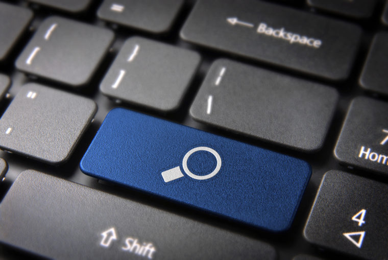 Internet search key with magnifying glass icon on laptop keyboard. Included clipping path, so you can easily edit it.