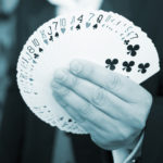 Playing cards spread out in hand of magician photo.