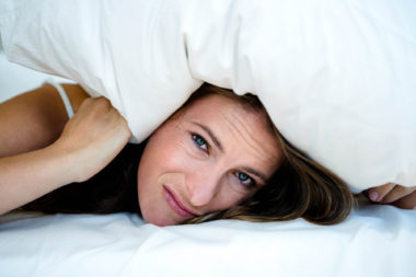 anxious woman hiding under a pillow, lying on her bed