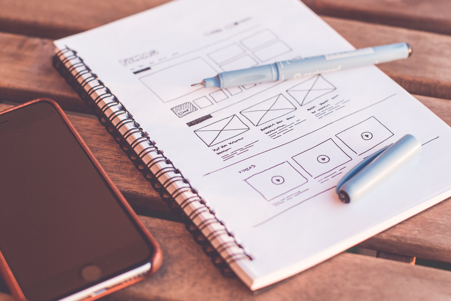 Notebook with design sketches beside an iPhone on a wooden table