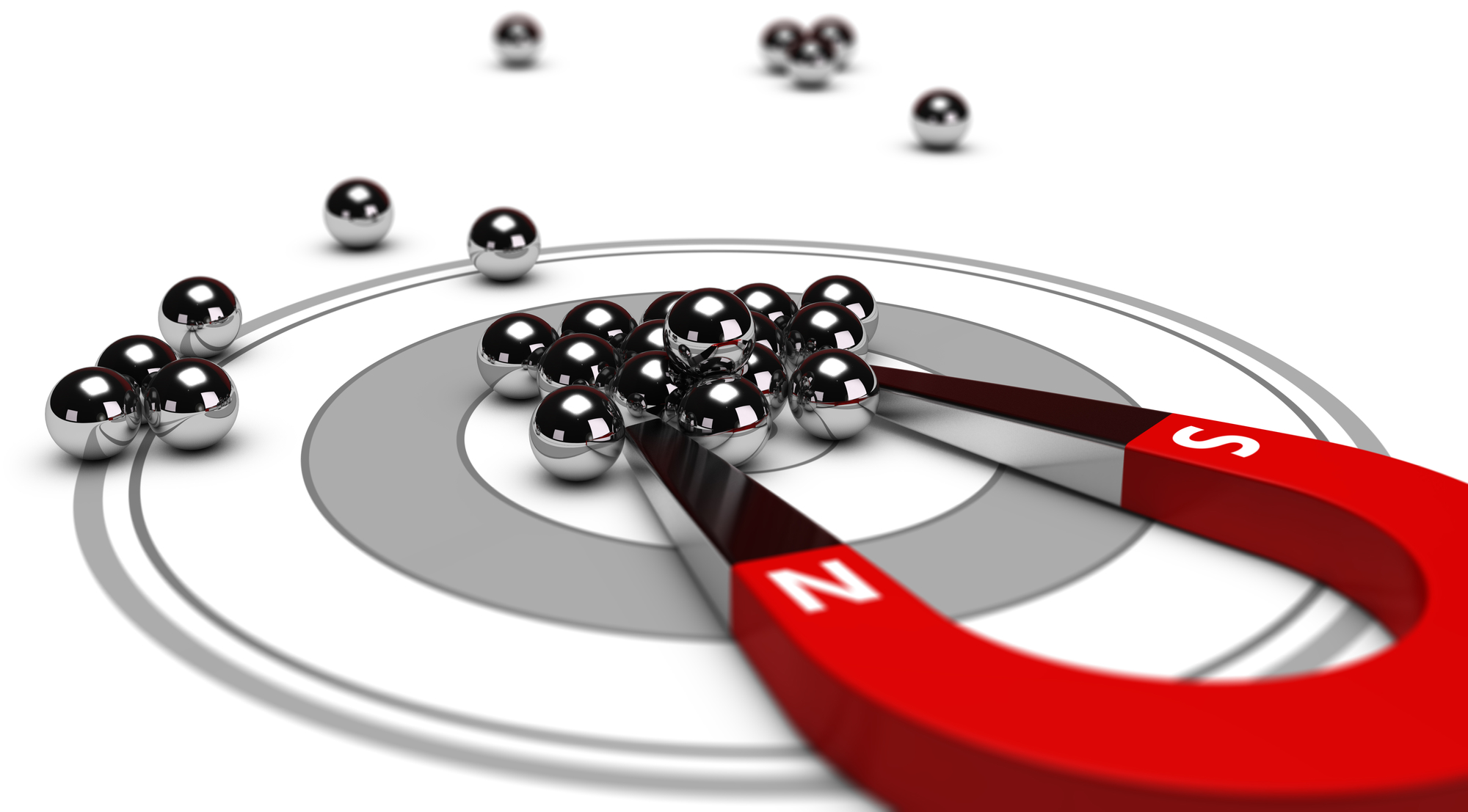 Horseshoe magnet attracting metal balls in the center of a grey target. Image concept of inbound marketing or advertising.