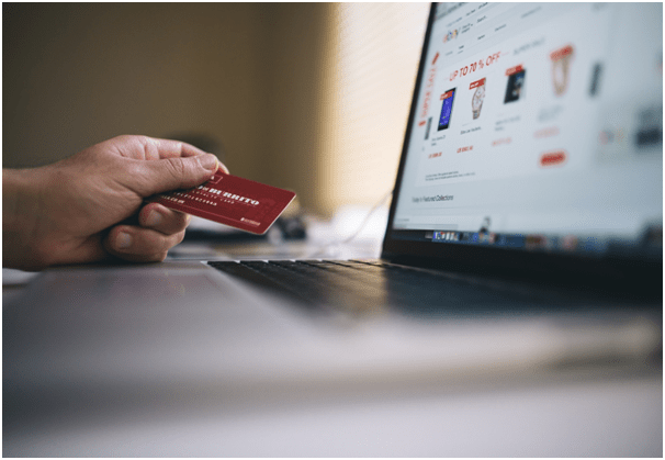 Shopper holding credit card while browsing through an online shopping site