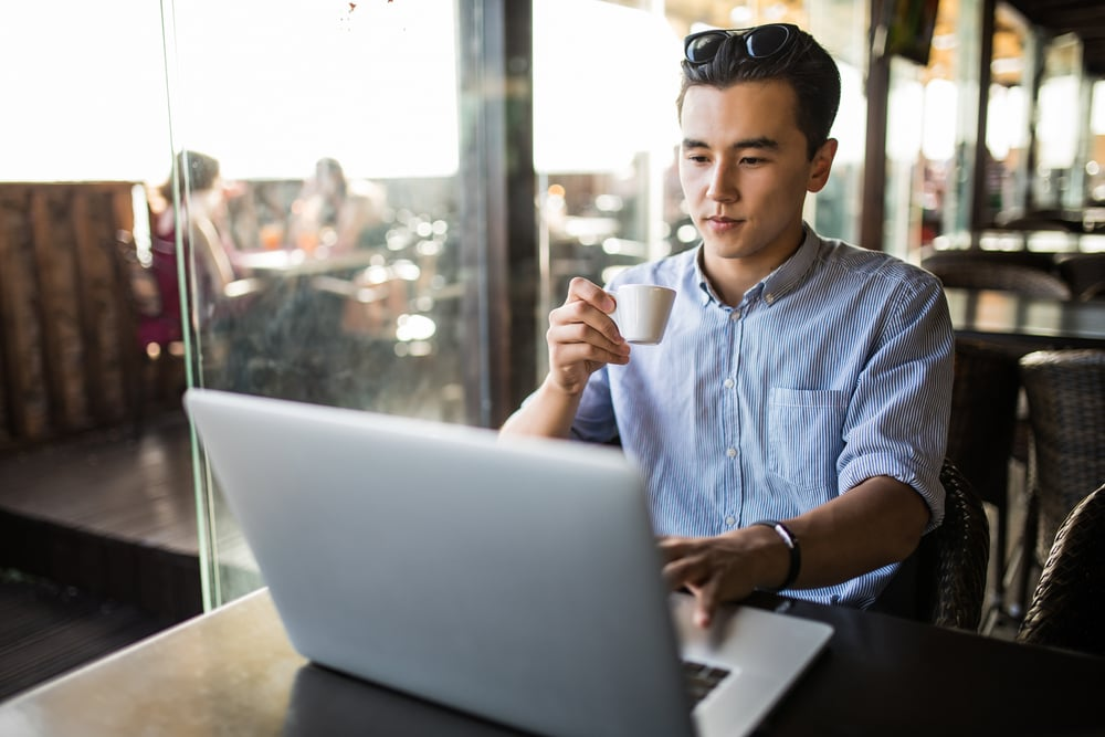 man-using-a-laptop-while-drinking-coffee