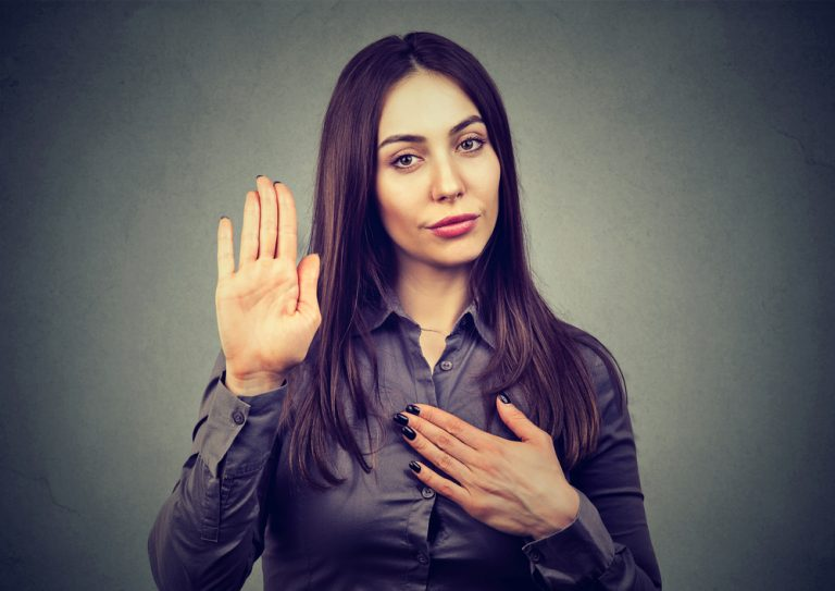 A woman holds up one hand and puts the other to her heart in a gesture of honesty.